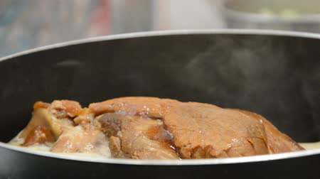 grille : braised pork leg with black Chinese herb soup boiling in cooking pot