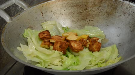 tofu : Iceberg lettuce and fried tofu cooking in iron pan on fire gas stove Stock Footage