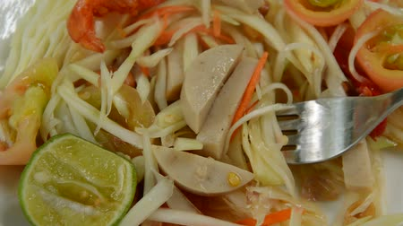 sarımsak : Som tum Thai spicy green papaya topping slice Vietnamese sausage salad scooping by fork Stok Video