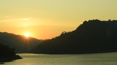 reservoir : sunrise behind mountain on river in Thailand Stock Footage
