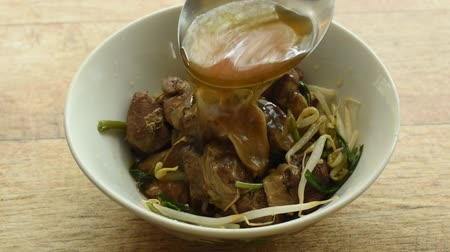 kavurma : ladle pouping brown soup on braised pork and bean sprout in bowl Stok Video