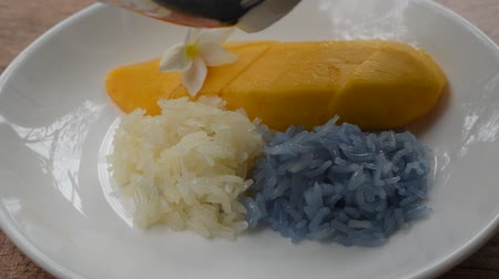 ripen mango with white and purple sticky rice dressing coconut milk on plate