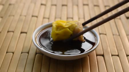 steamed Chinese pork dim sum pick by wooden chopsticks and dipping soy sauce on cup Стоковые видеозаписи