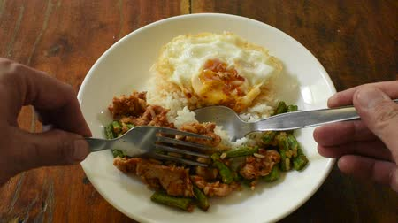 spicy stir fried pork with yard long bean curry topping egg on rice scooping by spoon and fork to eat
