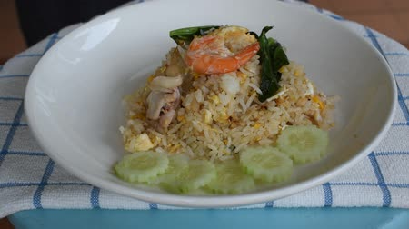 white onion : fried rice shrimp and seafood with Chinese kale squeezing lemon on plate scooping by spoon Stock Footage