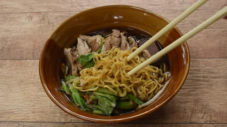 zeller : egg noodles with boiled duck in Chinese herb brown soup on bowl picking by chopsticks to eat Stock mozgókép