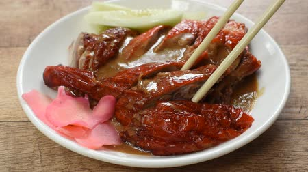 roasted duck meat and pickled ginger dressing sweet sauce picking by chopsticks on plate