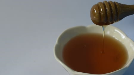 honey on wooden scoop drop to cup in white background Stok Video