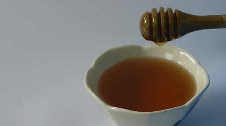 honey on wooden scoop drop to cup in white background Stockvideo