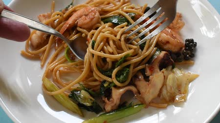cuttlefish : spicy stir fried spaghetti seafood with pepper and basil leaf rolling by silver fork for eat Stock Footage