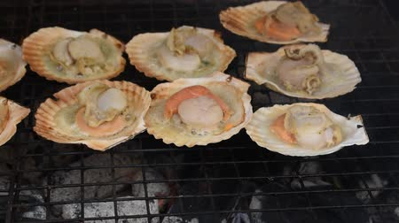 grilled scallop with butter and garlic by charcoal on iron gridiron