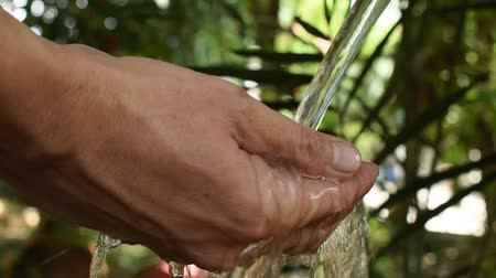 hand putting on water flow and splashing in garden Stok Video
