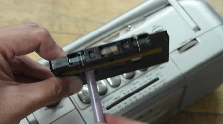 мегафон : hand putting pen in cassette hole for rolling tape with radio background