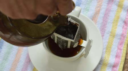 coffee drip mixed by hot water pouring from ceramic jar on cup