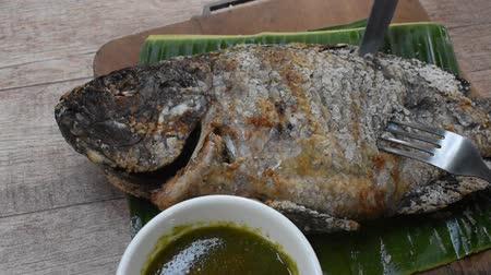 grilled mango fish wrapping salt slice skin off for eating Stok Video