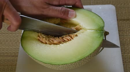 мускусная дыня : Japanese green melon cutting by knife on white plastic cutting board
