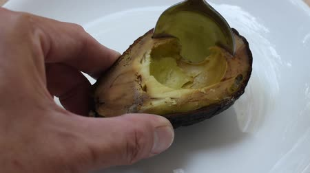 avocado half cutting on plate and scooping by silver spoon to eat