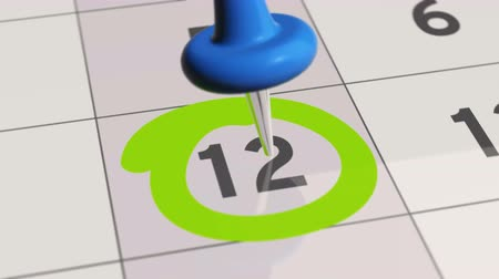 rajzszeg : Pin on the date number 12. The twelfth day of the month is marked with a blue thumbtack. 4K video animation. Stock mozgókép