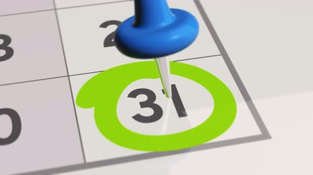 primeiro plano : Pin on the date number 31. The thirty first day of the month is marked with a blue thumbtack. 4K video animation. Stock Footage