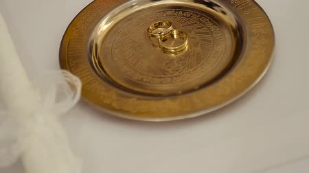 official : Wedding rings hanging on a golden plate