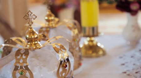 áldás : Church attributes for wedding ceremony. Gold crowns are on the altar. Attributes of priest. Interior of church Stock mozgókép