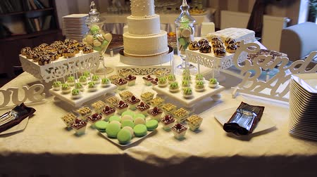 você : Tasty wedding reception candy bar dessert table inside celebration hall