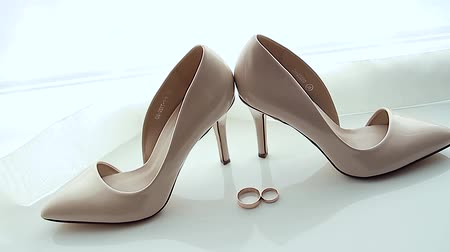 trouwen : Two wedding rings rolling together near brides wedding shoes Stockvideo