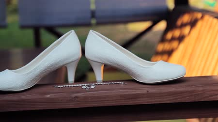 casar : Two wedding rings rolling together near brides wedding shoes Vídeos