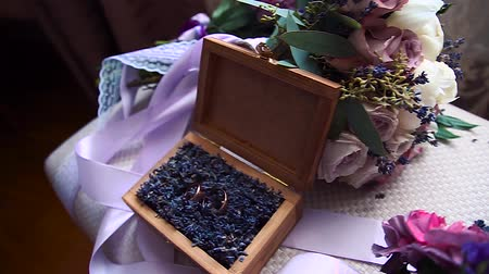 musgo : wedding rings in a wooden box filled with moss on the green grass. Wedding. Wedding ring. Vintage engagement ring with a precious stone lies in a wooden box with moss. The box on wooden table.