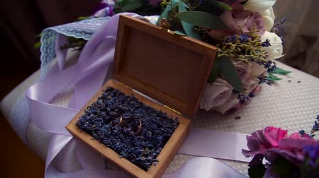 dois objetos : wedding rings in a wooden box filled with moss on the green grass. Wedding. Wedding ring. Vintage engagement ring with a precious stone lies in a wooden box with moss. The box on wooden table.