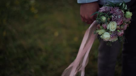 elegant dessert : The groom holds a bouquet with ribbons in the wind