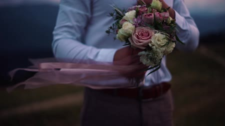 red tie : The groom holds a bouquet with ribbons in the wind
