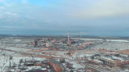 emise : Industrial factory and smoking chimney in winter city drone view. Smoke emission from industrial pipes on power plant aerial view. Smoking boiler pipes view from above
