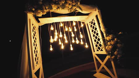 veranda : Lamps close up. Wedding garlands that glow on the arch. Vespers Wedding Ceremony Stok Video