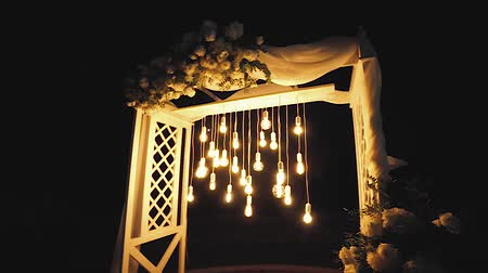 lâmpada elétrica : Lamps close up. Wedding garlands that glow on the arch. Vespers Wedding Ceremony Stock Footage