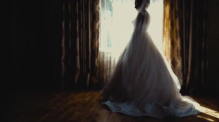 espartilho : Bride in silk dressing gown holding and admiring her beautiful wedding dress in front of the window. Wedding morning, brides preparations. Gorgeous bride in luxury dress is getting ready for wedding.