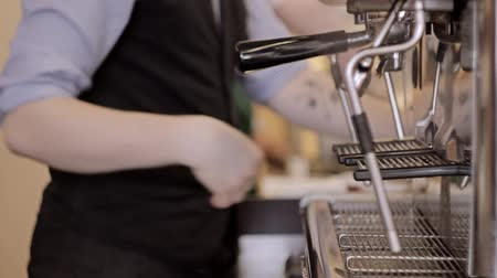 поздний завтрак : Barista tamping the grind coffee for espresso. Out of focus background.