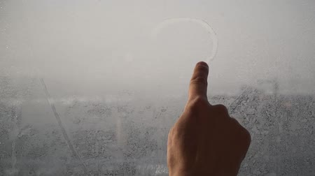 fogged : Finger draws heart at a window