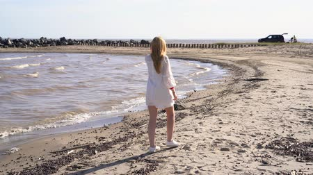 dalgakıran : Blond girl in a white dress walking along the shoreline