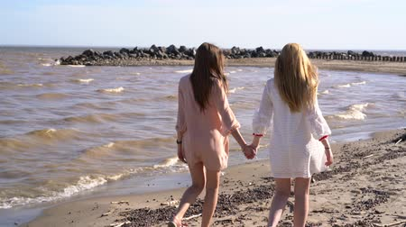 sicília : Two girls smiling and laughing, holding hands walking along the coastline Stock Footage