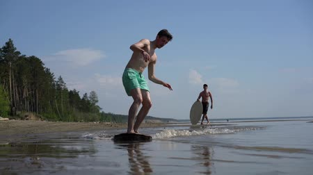 sicília : A young man skimboarding on the wild beach Stock Footage