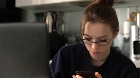 Attractive girl with glasses reads something on smartphone