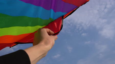 A colorful kite rotates around in hand close-up
