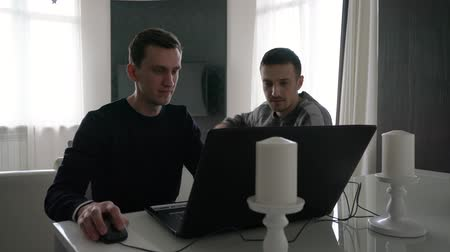 Two young men work with a laptop.