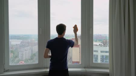 A man washes a window overlooking the city. Stock Footage