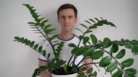 Portrait of a man with a plant in his hands.
