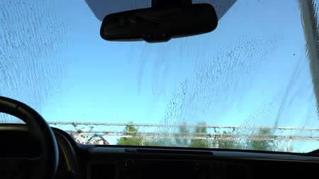 Washes the windshield at the car wash. View from the car. Stock Footage