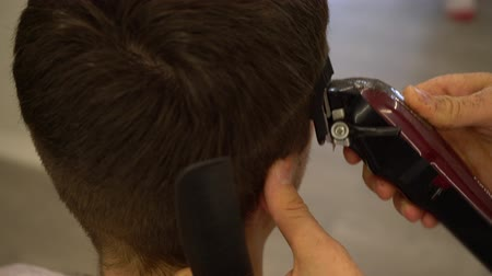 shaves : Barber shaves the hair on the head of a man with a hair clipper
