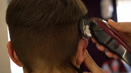 shaves : Barber shaves the hair on the head of a man with a hair clipper, close-up.