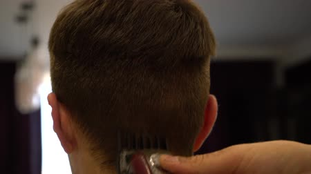 shaves : Hairdresser cuts guys hair with a machine closeup.